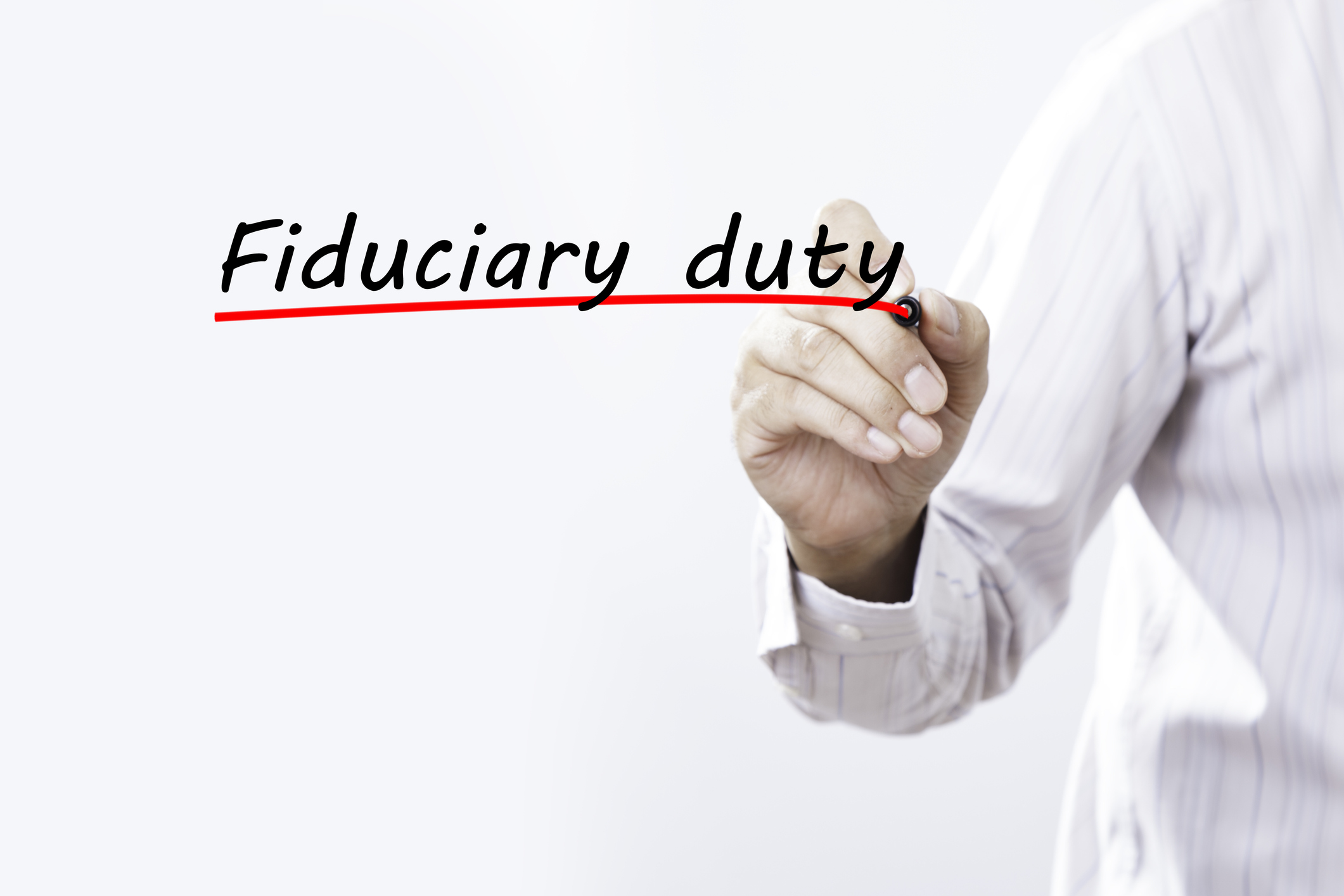 Businessman hand writing Fiduciary duty with red marker on transparent wipe board, business concept.
