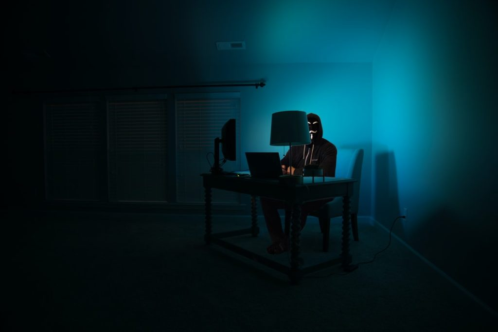 a long shot of a hacker in front of a computer