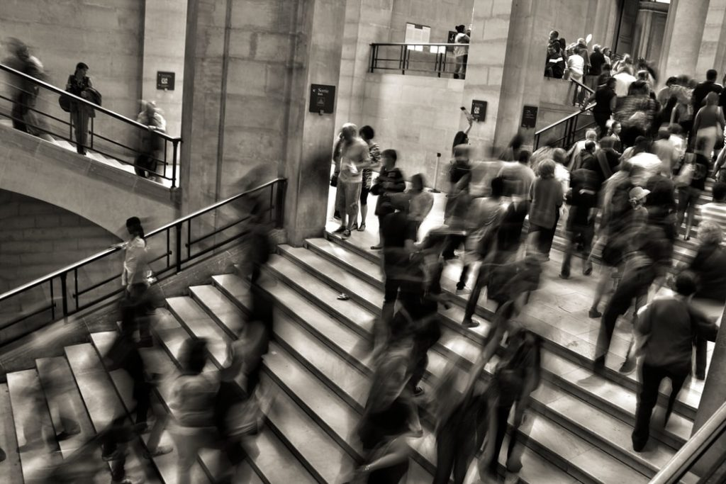 sepia photo of a crowd of people walking up and down a wide staircase