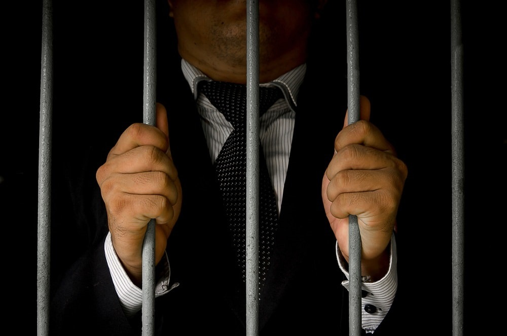 close up of a man holding onto prison bar