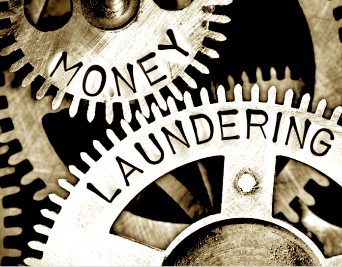 a sepia colored of two gear turning with the word 'Money Laudering' on it's gear