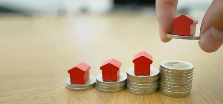 close up of finger holding a fourth red house on top of a coin about to stack it on top of a pile of coins.