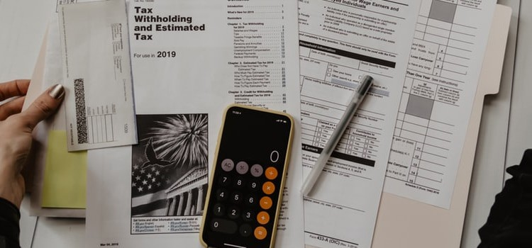 A table with tax forms and a calculator