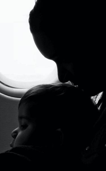 silhouette of a lady kissing the head of a toddler